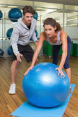 Trainer watching his client using exercise ball — 图库照片