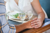 Couple holding hands at dinner — Photo