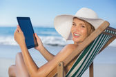 Woman relaxing in deck chair using tablet — Foto Stock