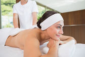 Beauty therapist rubbing womans back — Stock Photo