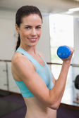 Woman lifting blue dumbbell — 图库照片
