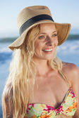 Blonde in straw hat smiling on beach — Photo