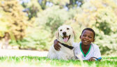Little boy lying with labrador — Stockfoto