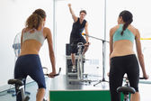 Women doing a spin class with instructor — Stock Photo