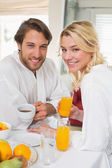 Couple in bathrobes having breakfast — Stock Photo