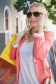 Blonde in sunglasses holding shopping bags — Foto Stock