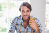 Smiling man having orange juice — ストック写真