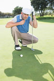 Golfer kneeling on the putting green — Stock fotografie