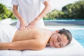 Szczęśliwy brunetka coraz masaż przy basenie — Zdjęcie stockowe