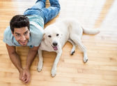 Man lying on floor with his labrador — Stock Photo