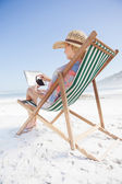Woman in deck chair using tablet — Stockfoto