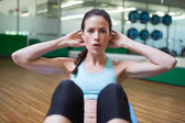 Brunette doing sit ups in fitness studio — ストック写真