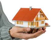 Hands showing a miniature model home — Stockfoto