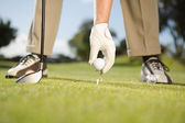 Golfer placing golf ball on tee — Stock Photo