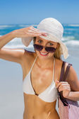 Blonde carrying bag on beach — Stock Photo