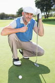 Golfer kneeling on the putting green — Stock Photo