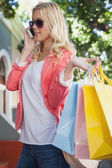 Blonde talking on phone holding shopping bags — Foto Stock