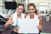 Fit friends showing white card — Stock Photo