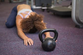 Woman lying in childs pose with kettlebell — Stock Photo