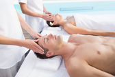 Couple enjoying head massages poolside — Stock Photo