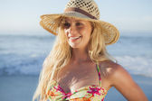 Blonde in straw hat and bikini on beach — Stock Photo