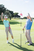 Golfing couple on the eighteenth hole — Stock Photo