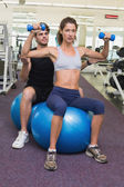 Trainer watching client lift dumbbells — ストック写真