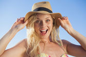Blonde in straw hat smiling on beach — Stock Photo
