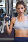 Fit woman using the weights machine — Stock Photo