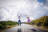Excited couple jumping on road — Stock Photo