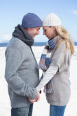 Couple on the beach in warm clothing — Stock Photo