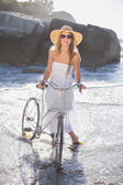 Blonde in sundress on bike at the beach — Stok fotoğraf