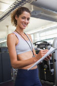 Fit trainer taking notes and smiling — Stockfoto