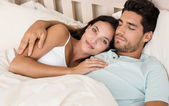 Couple lying in bed smile at camera — Stock Photo