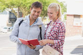 Tourist couple consulting the guide book — Stock Photo