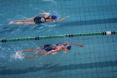 Female swimmers racing in pool — Zdjęcie stockowe