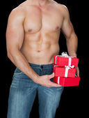 Muscular man holding presents — Stockfoto