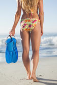 Woman holding flippers walking towards sea — Stock Photo
