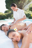 Сouple enjoying couples massage poolside — Stock Photo