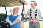Golfing couple on buggy — Stockfoto