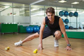 Fit man warming up in fitness studio — Stockfoto