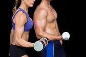 Bodybuilding couple with large dumbells — Stock Photo