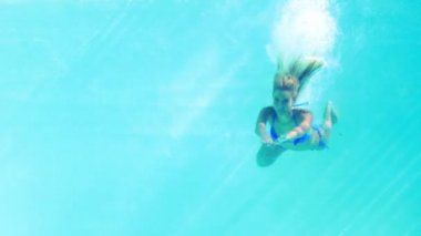 Sexy blonde in blue bikini jumping into the swimming pool — Stock Video