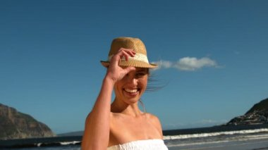 Smiling blonde taking off her sunhat on the beach — Stock Video