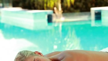 Peaceful blonde lying on massage table poolside — Stock Video
