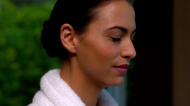 Beautiful brunette in bathrobe smiling at camera at the spa — Stock Video