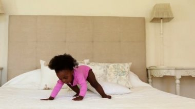 Baby girl standing and falling on bed — Vídeo Stock