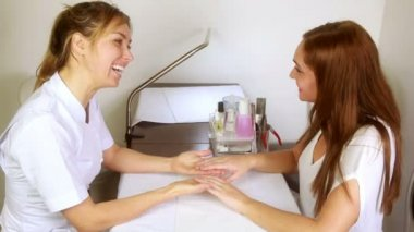 Smiling nail technician examining pretty customers hands — Wideo stockowe