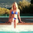 Beautiful blonde enjoying the sunshine in bikini sitting poolside — Stock Video #48880991