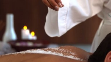 Beauty therapist pouring salt scrub on back — 图库视频影像